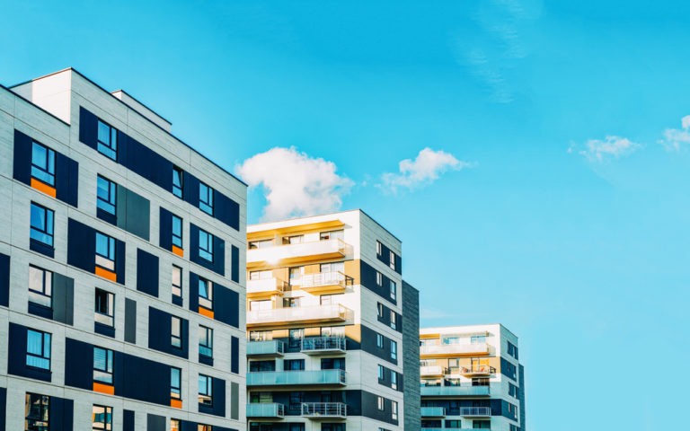 The exterior of apartment buildings on a sunny day.